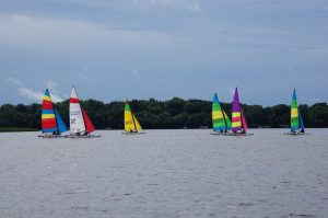 Six colorful sailboats on a lake with a dark blue sky in the background